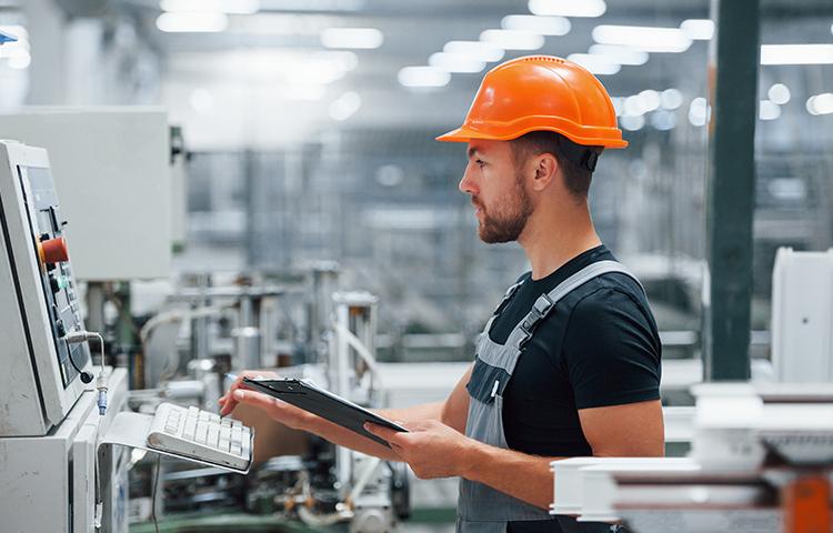 Angajat concentrat si eficient in hala industriala iluminata conform standardelor